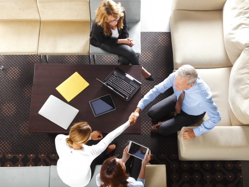 From above image of business people make a deal and shaking hands while sitting at meeting.